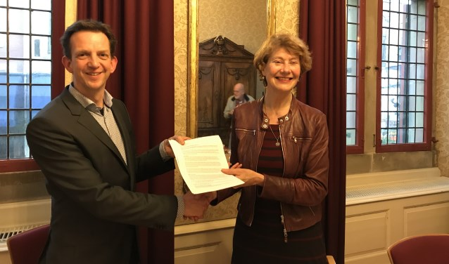 Informateur Marijke Vos (rechts) overhandigt haar rapport aan Frank van Vliet, fractievoorzitter van GroenLinks Delft (Foto: Annemarie de Vries)