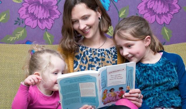 """Corina Schipaanboord laat haar kinderen Livia en Paola  haar boek zien. Over de vrolijke lay out zegt zij: """"Ik wilde graag een boek dat je gewoon op de tafel kunt leggen en dat niet ergens stiekem verstopt hoeft te worden.""""  foto: Carrie Frederiks"""