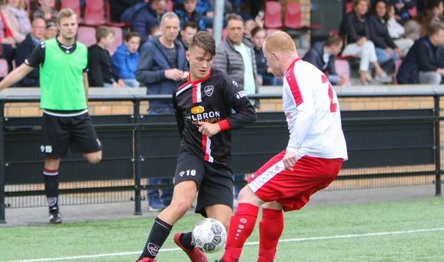 Foto: Julian Bril van VIOD in een duel om de bal met MASV verdediger Anthony Vogelaar (l).