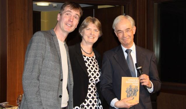 Auteurs Vincent van Stipdonk (links) en  Hester Tjalma overhandigen het eerste exemplaar aan Arie Jan Vos (BZK) (Foto: BZK).