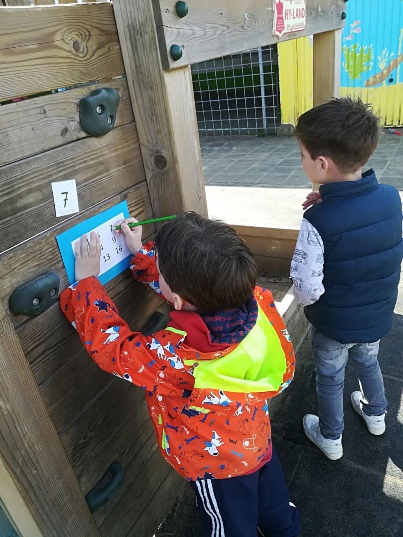 de kinderen van groep 1/2 zoeken op het schoolplein naar cijfers