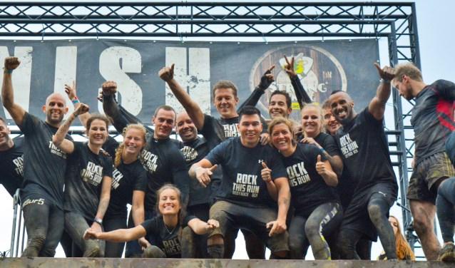 Enthousiaste groep obstacle runners bij de finish van een OCR-run