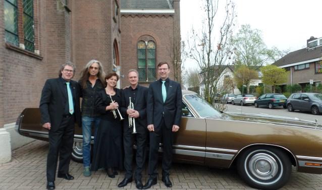Van links naar rechts: dirigent Peter Overduin, pianist Jan Vayne, trompettistenechtpaar Arjan en Edith Post en organist André de Jager voor één van de oude auto 's van Jan Vayne. De musici zetten hun talenten graag in ten behoeve van de kankerbestrijding.