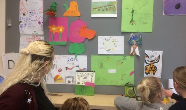 Kinderen laten trots hun gemaakte werk zien.