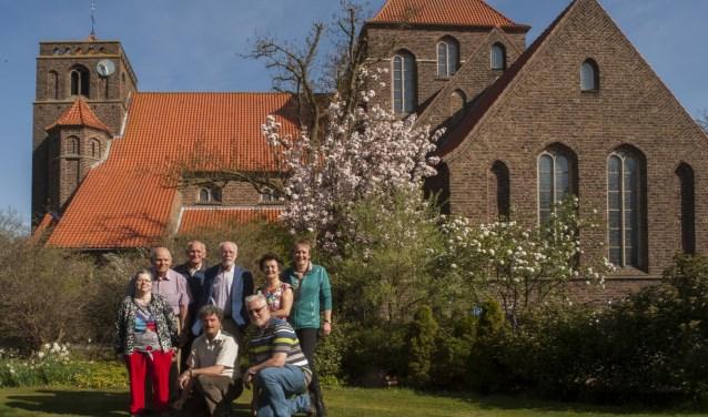 De expositiecommissie en kunstenares Jose van Druten poseren voor de St. Jozefkerk  in Achterveld. De renovatie van monumentale de kerk is het thema voor de jaarlijkse expositie die van 5 t/m 13 mei is te zien. (Foto: Hetty Heijne)
