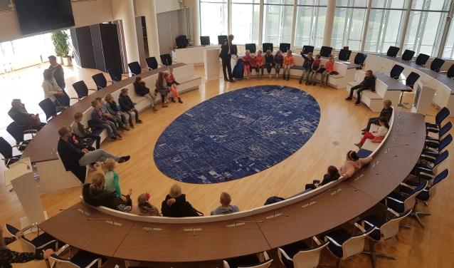 Wie nemen straks plaats in de raadzaal die op de foto wordt ingenomen door groep 3-leerlingen van de Patrimoniumschool. (Foto: archief)