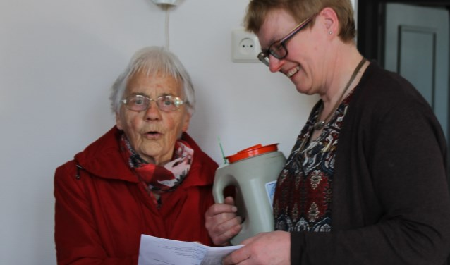 Marietje Stapelbroek-Hendriks was blij verrast met de bloemen en de bon.