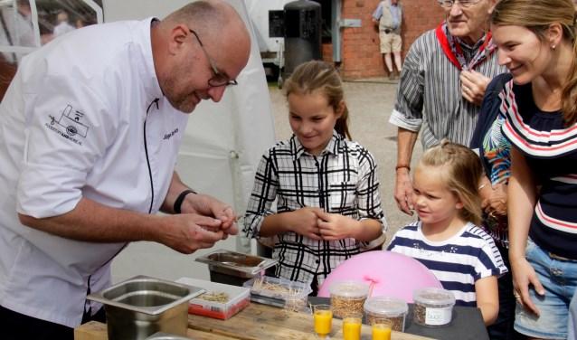 Een beeld van de vorige streekproductenmarkt bij Kaasboerderij Weenink: docent koksopleiding Jurgen Korthout laat bezoekers insecten proeven.