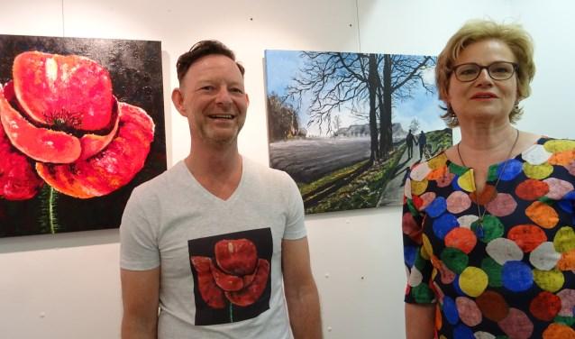 Henk Murraij (l) voor zijn schilderstuk 'Poppy' en Helma Kluft met haar werk 'Samen op pad'. Hun schilderwerk is te bezichtigen in Het Hedels Historisch Museum in Hedel. Foto: Mieke Boelen