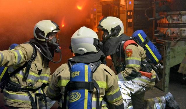 Bevelvoerder Jarno (r) overlegt met zijn manschappen Bertil en Gelieny van de aanvalsploeg over de vorderingen van de inzet tijdens een brandoefening bij de Kargro in Montfoort. (Foto: Paul van den Dungen)