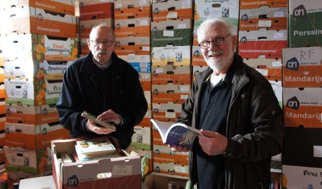"""Rob van Deijk(links) en Koert Verlind tussen de dozen vol met boeken. """"Het is jaarlijks een hele organisatie, maar het is de moeite meer dan waard."""" (Foto: Thea van der Raaf)"""