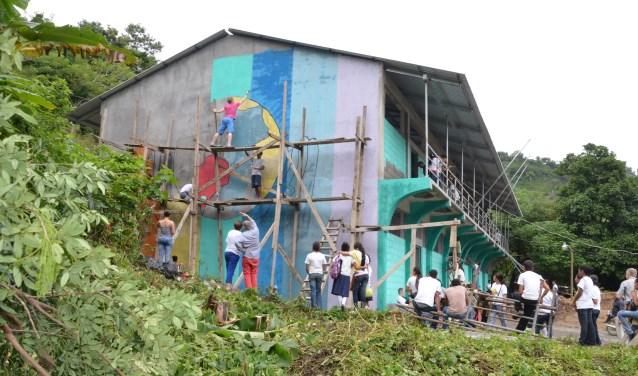 Allard Froon helpt bij de muurschildering op het gebouw vlak voor de opening in november 2012. (foto: Sonja Froon-Bron
