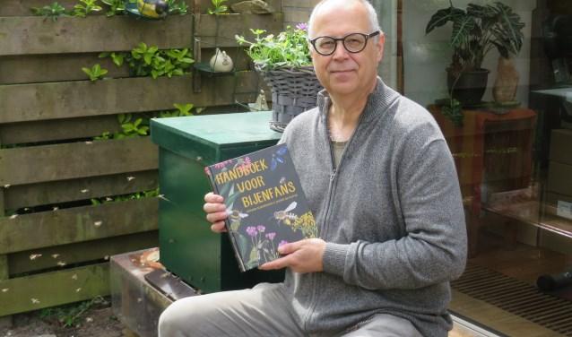 Gerard Sonnemans toont zijn Handboek voor bijenfans.