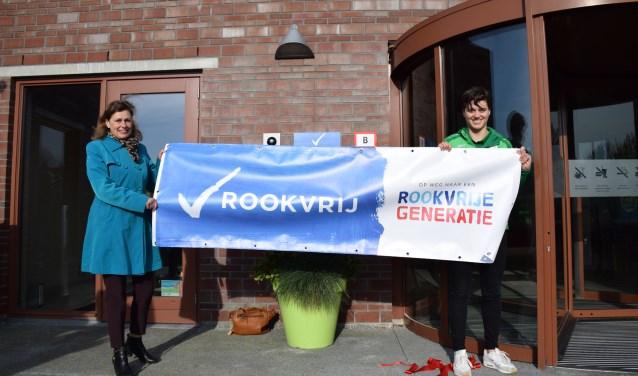 Wethouder Corine Dijkstra (l) en Aafke van Leeuwen onthullen de eerste rookvrije zone bij het Groenhovenbad. Foto: PR