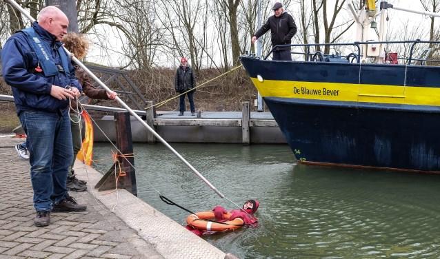 De bemanning van de Blauwe Bever oefent in de thuishaven in Wageningen de situatie man over boord. Dat gebeurde op een ijskoude zaterdag in maart. (Foto Max Timons)