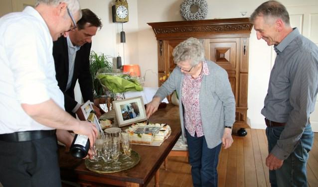 Christa Cohrs snijdt de taart aan ter gelegenheid van haar honderdste verblijf op de Korenhorst, onder toeziend oog van Pim Davids die de champagne inschenkt, daarnaast Clemens Ambting en rechts Willy Bus. (foto: Elsie Schoorel)