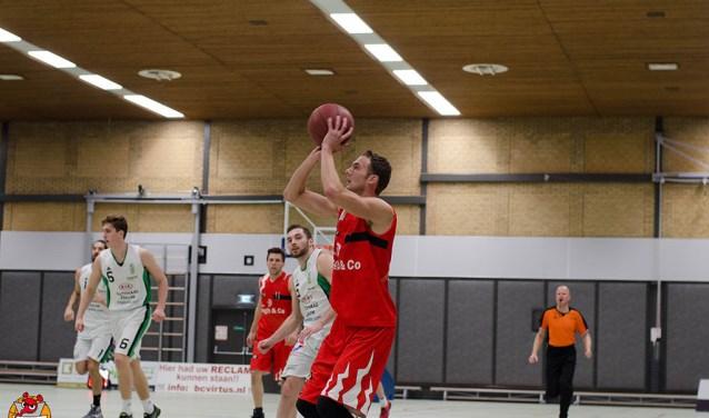 Niels Plieger scoort twee van zijn 20 punten. Door de zege heeft Virtus zich in een uitstekende positie gemanoeuvreerd om zaterdag in eigen huis voor de tweede keer kampioen te worden in de landelijke Eerste Divisie B van de Nederlandse Basketbal Bond. Foto: Martijn Visser