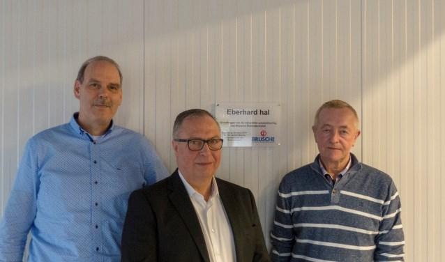 Van links naar rechts voor het naambordje van de uitbreiding van de werkplaats: Bertus Wetering en Hennie Nijhuis (directie) en Henk Eberhard (jubilaris)