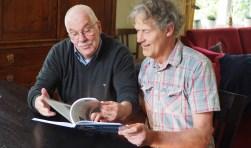 Gé Scholten (links) en Henk Sieben werpen een blik in het boek over de geschiedenis van het voetbal in Eibergen. Foto: Arie Burggraaf.