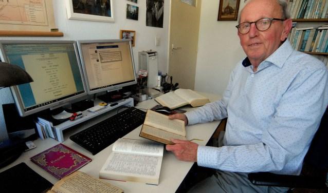Tiemen van Kampen met in zijn hand en op het bureau enkele geredde Hebreeuwse gebedsboeken. (foto: Tom Oosthout)