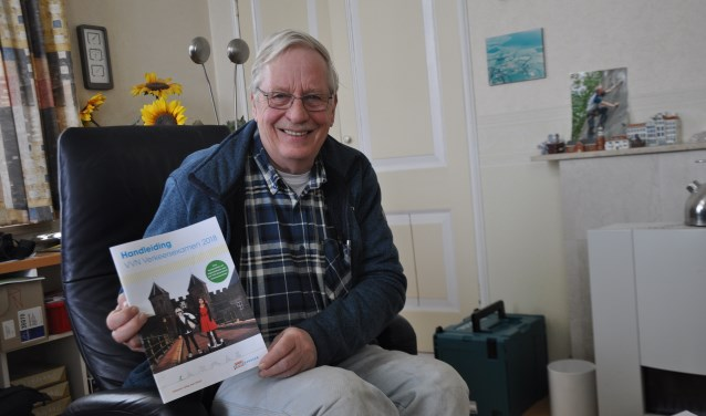 Gerard Oele met de VVN-handleiding. Daarnaast is er nog een zeer uitgebreid draaiboek om de verkeersexamens te organiseren. FOTO: Anneke Flikweert