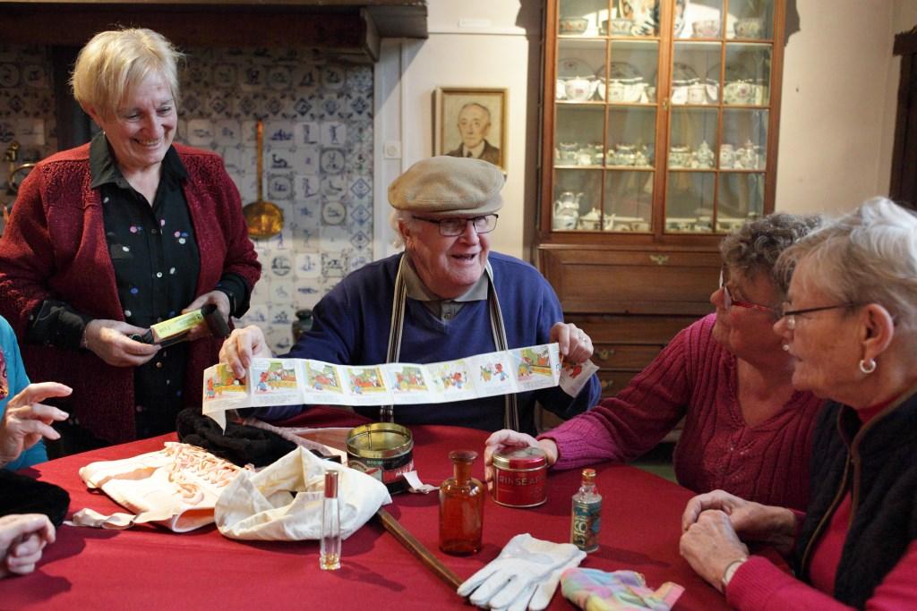 Een vrijwilliger van Stichting Feest van Herkenning haalt herinneringen op met 'De winkel van Sinkel' Fotoatelier Karin den Boer © Persgroep