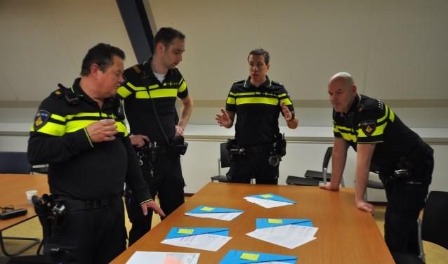 Een aantal agenten ordent de binnengekomen aanvragen. Van links naar rechts Freek Hullekes, Jan Willem van Bree, Richard den Boer en Chris van der Veen. FOTO: Anneke Flikweert