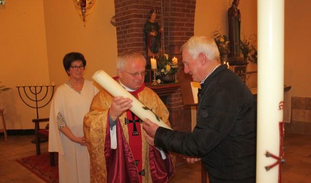 Gerrit Schopman ontvangt de paaskaars 2017 uit handen van pastoor Theo Munsterhuis. Foto: delutte.com