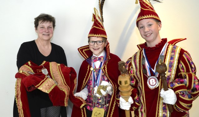 Jeugdadjudant Giel (midden) en jeugdprins Max overhandigen attributen aan Ingrid Mens, hoofd van de museumcollecties bij Kunstwerk! Liemers Museum. (foto: Ab Hendriks)