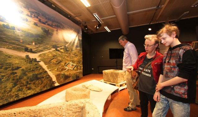 Thorben van de Noort bekijkt met zijn moeder Paula de archeologische vondsten in Bemmel. Hij heeft Grieks en Latijn in zijn vakkenpakket en dat wakkert de interesse aan voor oudheidkundige zaken. Op de expositie in De Kinkel kwam veel publiek af. (foto: Kirsten den Boef)