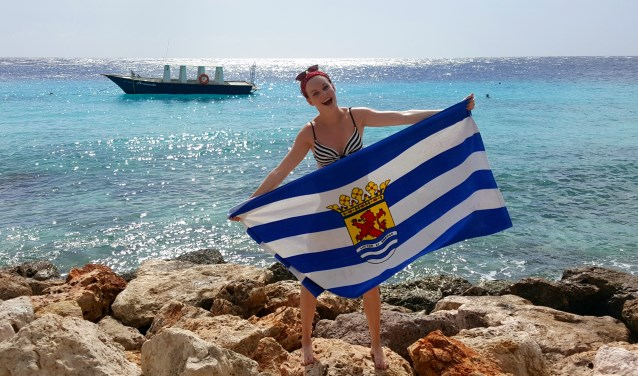 Elodie aan het strand met een heuse 'Zeeuwse vlag-badhanddoek', een afscheidscadeautje van haar PZC-collega's.