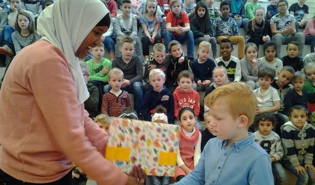 De oudste leerling van de school overhandigt een cadeau aan de jongste leerling, Milan.