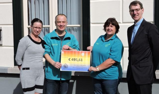 Resy van Amstel, bestuurslid van C.C.V. Schoenlapperslaand, overhandigt de cheque aan Miranda v.d. Westen en Jan van Geffen van Stichting Ambulance Wens Nederland. Dit in het bijzijn van pastoor Dorssers.