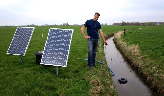 Sjoerd Witteman bij de zonnepomp in zijn land in de Meerpolder. 'We doen dit graag voor de weidevogels.' Foto: Simone Langeveld