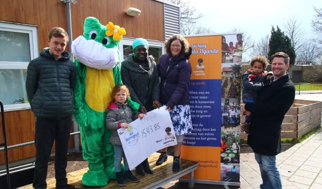 Milan en Lynn overhandigen de cheque aan vrijwilligers Stichting Upenda Uganda.