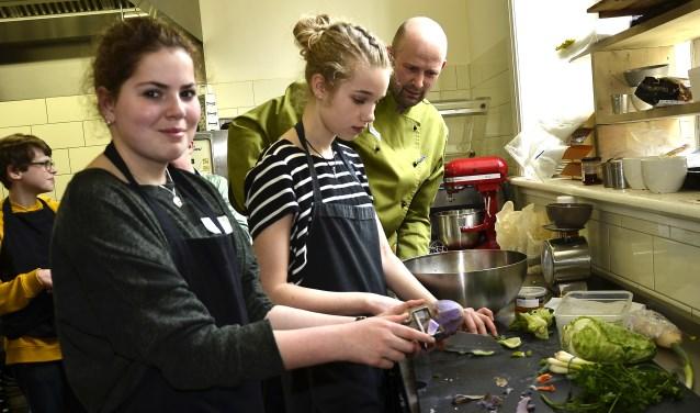 Julia (links) en Iris snijden de groenten op het aanrecht in de keuken van Restaurant Eet-Lokaal. Ze bereiden een maaltijd die bestaat uit Afrikaanse gerechten. Kok Marck Hofmeester kijkt met belangstelling toe. (Foto: Ab Hendriks)