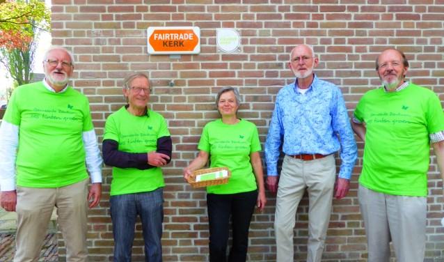 Een deel van de projectgroep van de Vredebergkerk met als tweede van links Teun van Eck. Aan de Vredebergkerk hangen bordjes Fairtrade Kerk en daarnaast (minder goed leesbaar) sinds kort ook Groene Kerk. (foto: Marnix ten Brinke)