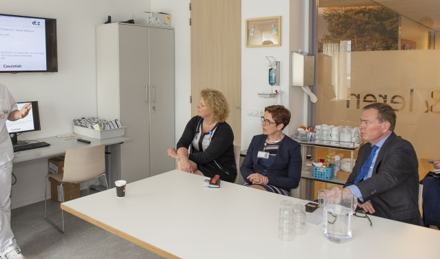 Oncologieverpleegkundige René Leijtens geeft aan minister Bruno Bruins uitleg over het zorgpad voor longkankerpatiënten. Zorgmanager Rita Arts (link aan tafel) en ETZ-bestuurder Anita Wydoodt luisteren mee.