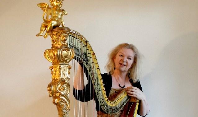 """Regina Ederveen met de 199-jarige Érard-harp: """"Die engel zit er al sinds 1819 bovenop, in volle glorie!"""" (Eigen foto)"""