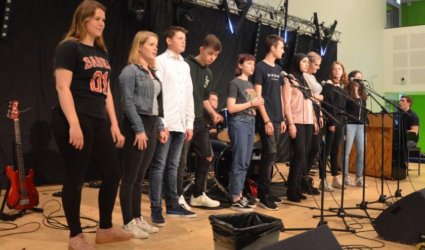 Tijdens het interview was het podium in de aula ingericht voor het concert van de leerlingen die muziekexamen doen. Achter de piano muziekdocent Bas Koolenbrander. FOTO: Ben Blom