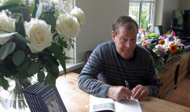 Eibert Pieper signeert een exemplaar van het boek over zijn leven. Hij is blind, maar liet zich niet tegenhouden om te judoën en andere sporten te doen. FOTO: Yvonne Pieper.