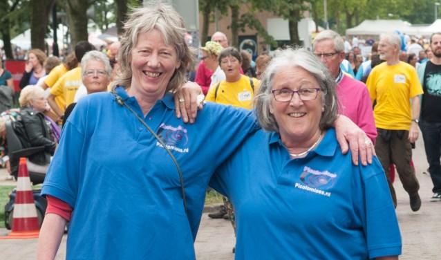 De oprichters van het Osse gezelschap, Beppie Lotterman (links) en Truus Burghouwt tijdens Samenloop voor Hoop. Zij startten in 2008 met een klein groepje. Inmiddels is het koor Picolomioss  uitgegroeid tot een flink gezelschap met vijftig zangeressen en zangers.
