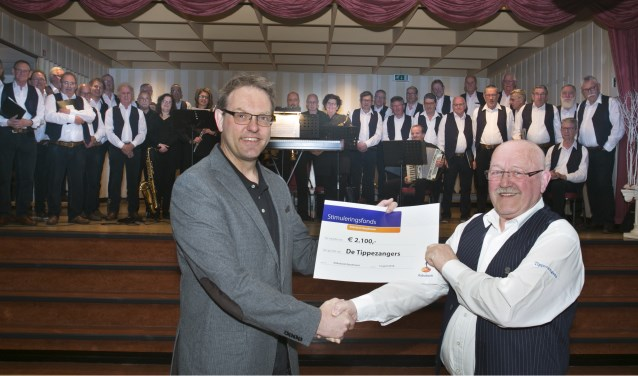 Jan Teunissen neemt cheque in ontvangst van Dhr. Stoffersen namens de Rabobank.