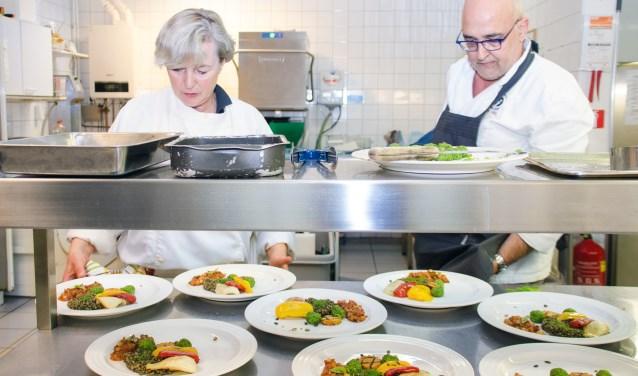 Iedere derde vrijdag van de maand worden de heerlijkste gerechten bereid. Na een laatste kritische blik van Adrie Wisse en Anneke van Hootegem kan het hoofdgerecht worden opgediend. FOTO: Carrie Frederiks