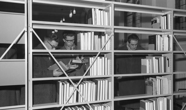 Drie mannen bladeren geïnteresseerd door de boeken in een leeszaal.