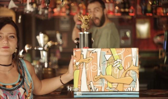 Yonne van Gastel en Jack Siemons van Bruin Café JaxX poseren met artwork van de Roosendaal-750-Geniet-Tour. Mensen kunnen bij 29 horecazaken stempels krijgen om te sparen voor exclusieve speldjes.