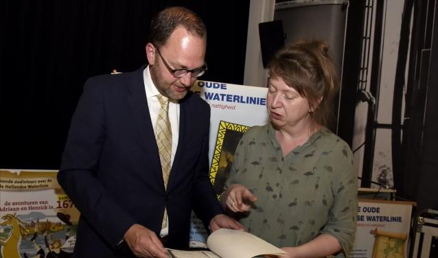 Burgemeester Milo Schoenmaker bekijkt samen met Coretta Bakker van het Streekarchief de doop- en sterfboeken uit het Goudse  rampjaar 1673. Foto's: Marianka Peters