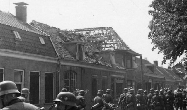 Duitse troepen trekken in mei 1940 door het zwaar gehavende Scherpenzeel. Een niet eerder gepubliceerde foto uit een serie van drie. (Foto coll.: Vincent van Rijn/Nieuw-Vennep)