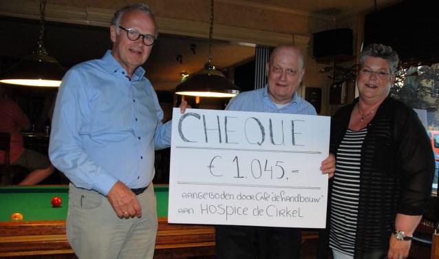 De cheque wordt overhandigd aan  bestuursvoorzitter Ad van Driel.