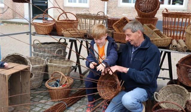 Mandenmaker Riens Booy weet heel wat te vertellen over zijn ambacht. En jongeren mogen hem zelfs helpen bij het vlechten van een mand of korf. FOTO:PR